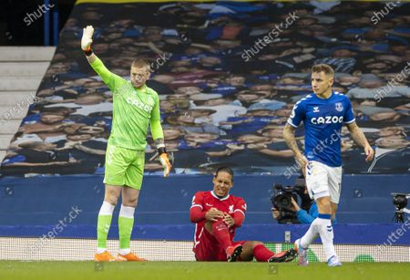 Everton's goalkeeper Jordan Pickford (L) reacts as Liverpool's Virgil van Dijk (C) sits injured during the Premier League match between Everton FC and Liverpool FC at Goodison Park in Liverpool, Britain, on Oct. 17, 2020. The game ended in a 2-2 draw.