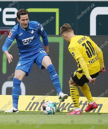 Emre Can (L) of Dortmund vies with Jacob Bruun Larsen of Hoffenheim during a German Bundesliga match between Borussia Dortmund and TSG Hoffenheim in Hoffenheim, Germany, Oct. 17, 2020.