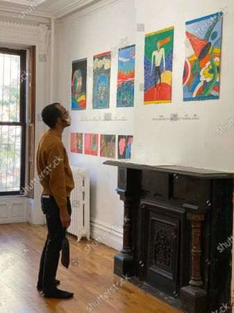 A visitor looks at Chen Dongfan's works at FOU Gallery in New York, the United States, on Oct. 17, 2020. More than 50 works of Chen Dongfan, a Chinese painter living in New York City, which were created during the time of COVID-19, are on display at Fou Gallery starting Saturday. (Photo by Inna Xu/Xinhua) TO GO WITH Chinese artist presents paintings created during pandemic - Inna Xu -