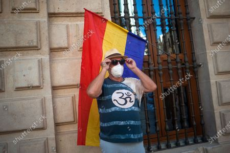 A protester wearing a face mask seen adjusting his sunglasses in front of a republican flag at Plaza de la Aduana square during the demonstration. Protesters called for an end to the Spanish monarchy after the sudden departure of the former King Juan Carlos from the country this week amid a corruption scandal. Juan Carlos, who abdicated in 2014 in favor of his son Felipe, abruptly announced his decision to leave, but there has been no official confirmation of where he went, setting off an international guessing game.