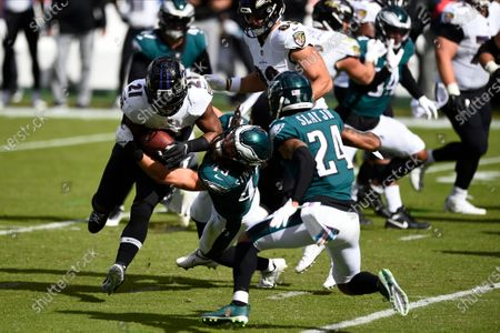 Baltimore Ravens' Mark Ingram II (21) is tackled by Philadelphia Eagles' Alex Singleton (49) during the first half of an NFL football game, in Philadelphia