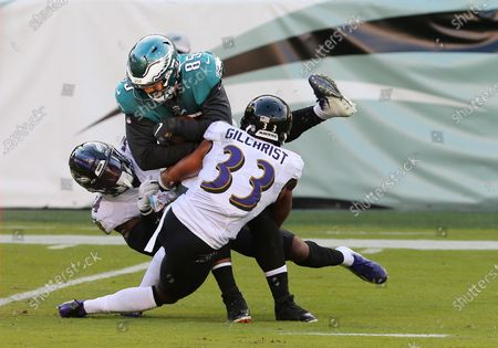 Philadelphia Eagles' Richard Rodgers (85) is tackled by Baltimore Ravens' Tyus Bowser (54) and Marcus Gilchrist (33) after a run during the third quarter of an NFL football game, in Philadelphia. The Ravens defeated the Eagles 30-28