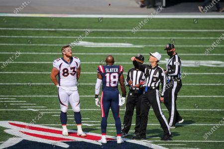 Stock Image of Denver Broncos tight end Andrew Beck (83) and New England Patriots special teams captain Matthew Slater (18) watch as referee Scott Novak (1) flips the coin prior to an NFL football game, in Foxborough, Mass