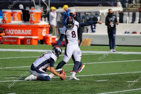 Denver Broncos punter Sam Martin (6) holds the ball for place kicker Brandon McManus (8) prior to an NFL football game against the New England Patriots, in Foxborough, Mass