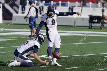 Denver Broncos place kicker Brandon McManus (8) warms up as punter Sam Martin (6) holds before an NFL football game against the New England Patriots, in Foxborough, Mass