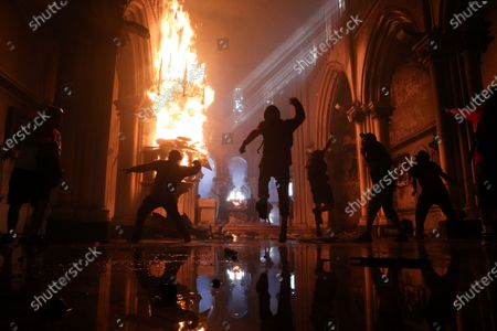 Protesters attack San Francisco de Borja church, which belongs to the military police, during the one year anniversary of the start of massive anti-government protests triggered by increased subway fare, which led to demands for social change nationwide in Santiago, Chile, . The protests led the government to schedule a constituent plebiscite, set for Oct. 25, that seeks to change the country's constitution written during the nation's military dictatorship