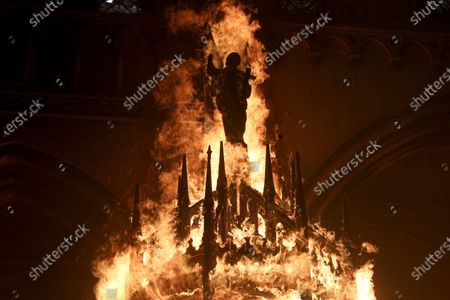 Saint figure burns after protesters storm the San Francisco de Borja church, that belongs to Carabineros, Chile's national police force, on the one-year anniversary of the start of anti-government mass protests over inequality in Santiago, Chile