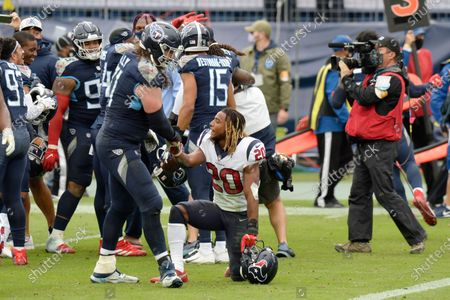 Tennessee Titans offensive tackle Dennis Kelly (71) shakes hands with Houston Texans strong safety Justin Reid (20) after an NFL football game, in Nashville, Tenn. The Titans won 42-36 in overtime