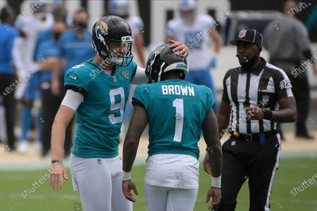 Jacksonville Jaguars holder Logan Cooke (9) pats place kicker Jon Brown (1) on the head after Brown kicked a field goal against the Detroit Lions during the first half of an NFL football game, in Jacksonville, Fla