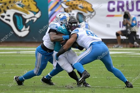 Jacksonville Jaguars running back James Robinson (30) is sandwiched between Detroit Lions outside linebacker Jamie Collins (58) and defensive end Trey Flowers (90) after rushing for yardage during the first half of an NFL football game, in Jacksonville, Fla