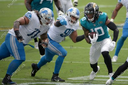 Jacksonville Jaguars wide receiver Laviska Shenault Jr. (10) is tackled by Detroit Lions nose tackle Danny Shelton (71) and defensive end Trey Flowers (90) after catching a pass during the first half of an NFL football game, in Jacksonville, Fla