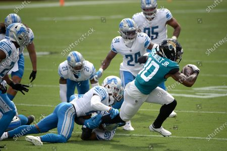 Jacksonville Jaguars wide receiver Laviska Shenault Jr. (10) is tackled by Detroit Lions cornerback Darryl Roberts and defensive end Trey Flowers (90) after catching a pass during the first half of an NFL football game, in Jacksonville, Fla