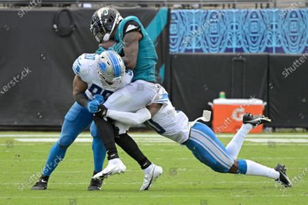 Jacksonville Jaguars wide receiver D.J. Chark is sandwiched between Detroit Lions defensive end Trey Flowers (90) and cornerback Jeff Okudah, right, after catching a pass during the second half of an NFL football game, in Jacksonville, Fla