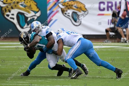 Jacksonville Jaguars running back James Robinson (30) is tackled by Detroit Lions outside linebacker Jamie Collins (58) and defensive end Trey Flowers (90) after rushing for yardage during the first half of an NFL football game, in Jacksonville, Fla