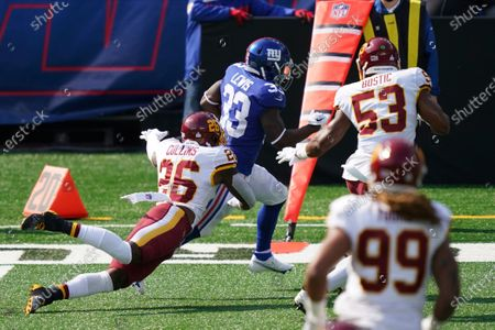 Washington Football Team's Landon Collins (26) and Jon Bostic (53) force New York Giants' Dion Lewis (33) out of bounds during the first half of an NFL football game, in East Rutherford, N.J