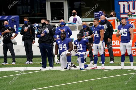New York Giants' Dalvin Tomlinson (94) and Jabrill Peppers (21) take a knee during the playing of the national anthem before an NFL football game against the Washington Football Team, in East Rutherford, N.J