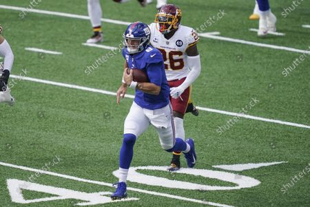 New York Giants' Daniel Jones (8) runs away from Washington Football Team's Landon Collins (26) during the first half of an NFL football game, in East Rutherford, N.J