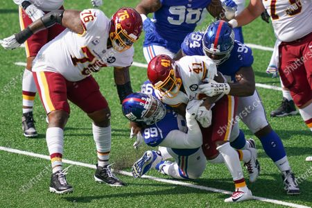 New York Giants' Leonard Williams (99) and Dalvin Tomlinson (94) tackle Washington Football Team's J.D. McKissic (41) as Morgan Moses (76) watches during the first half of an NFL football game, in East Rutherford, N.J