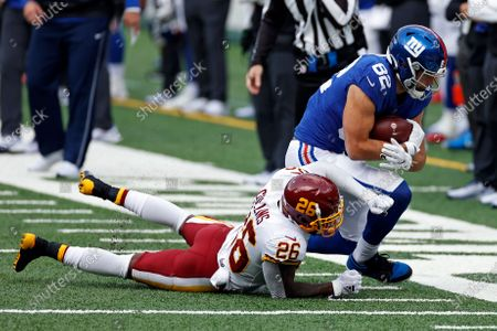 New York Giants tight end Kaden Smith (82) is tackled by Washington Football Team strong safety Landon Collins (26) during an NFL football game, in East Rutherford, N.J