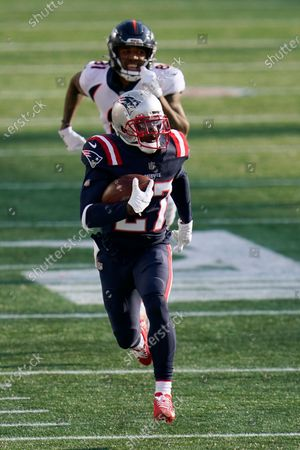 New England Patriots defensive back J.C. Jackson runs with the ball after intercepting a pass intended for Denver Broncos wide receiver Tim Patrick, rear, in the second half of an NFL football game, in Foxborough, Mass