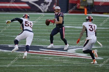 New England Patriots wide receiver Julian Edelman, center, looks for a receiver as he attempts to pass between Denver Broncos linebacker Bradley Chubb, left, and safety Justin Simmons, right, in the second half of an NFL football game, in Foxborough, Mass