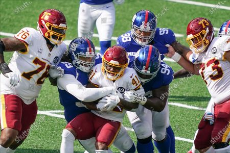 New York Giants' Leonard Williams (99) and Dalvin Tomlinson (94) tackle Washington Football Team's J.D. McKissic (41) during the first half of an NFL football game, in East Rutherford, N.J