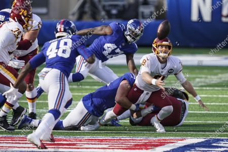 Washington Football Team quarterback Kyle Allen (8) loses control of the ball during the second half of an NFL football game against the New York Giants, in East Rutherford, N.J. Giants linebacker Tae Crowder (48) recovered the ball and scored a touchdown on the play