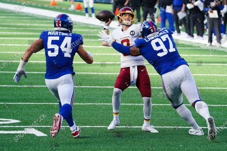 Stock Picture of New York Giants defensive tackle Dexter Lawrence (97) and Blake Martinez (54) rush Washington Football Team quarterback Kyle Allen (8) during a point after try in the second half of an NFL football game, in East Rutherford, N.J. The point after try was unsuccessful