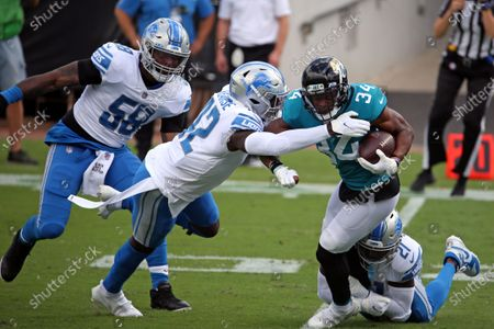 Jacksonville Jaguars running back Chris Thompson (34) fights for yardage against Detroit Lions linebacker Jamie Collins Sr. (58), safety Jayron Kearse, center, and safety Tracy Walker (21) during the first half of an NFL football game, in Jacksonville, Fla