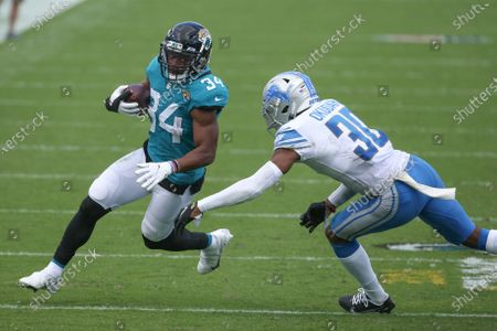 Jacksonville Jaguars running back Chris Thompson (34) tries to get around Detroit Lions cornerback Jeff Okudah, right, on a run-ing play during the second half of an NFL football game, in Jacksonville, Fla