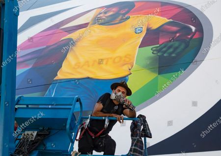 Brazilian street artist Eduardo Kobra poses in front of the mural he painted to pay homage to soccer legend Pele to mark his 80th birthday in the coastal city of Santos, Brazil, . Pele's actual birthday is Oct. 23