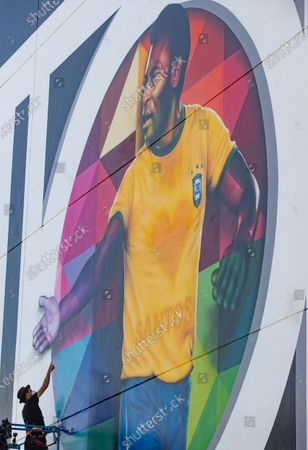Brazilian street artist Eduardo Kobra spray paints the finishing touches to his mural to pay homage to soccer legend Pele to mark his 80th birthday in the coastal city of Santos, Brazil, . Pele's birthday is Oct. 23