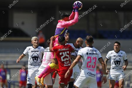 Pumas' goalkeeper Alfredo Talavera, top, catches the ball during a Mexican soccer league match against Toluca at University Olympic Stadium in Mexico City, . The match was played without fans as a precaution against the coronavirus