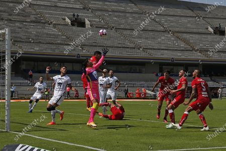 Pumas' goalkeeper Alfredo Talavera jumps for the ball challenged by Toluca's Kevin Castaneda during a Mexican soccer at University Olympic Stadium in Mexico City