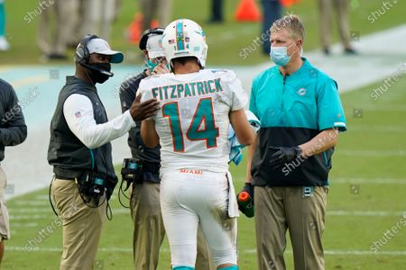 Miami Dolphins quarterback Ryan Fitzpatrick (14) talks to head coach Brian Flores during the first half of an NFL football game against the New York Jets, in Miami Gardens, Fla