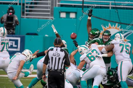 Miami Dolphins kicker Jason Sanders (7) kicks an extra point as Miami Dolphins guard Michael Deiter (63) and Miami Dolphins offensive lineman Ereck Flowers (75) block New York Jets defensive lineman Steve McLendon (99) and New York Jets defensive lineman Henry Anderson (96) during an NFL football game, in Miami Gardens, Fla