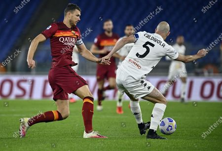 Roma's Edin Dzeko (L) in action against Benevento's Luca Caldirola (R) during the Italian Serie A soccer match between AS Roma and Benevento Calcio at the Olimpico stadium in Rome, Italy, 18 October 2020.