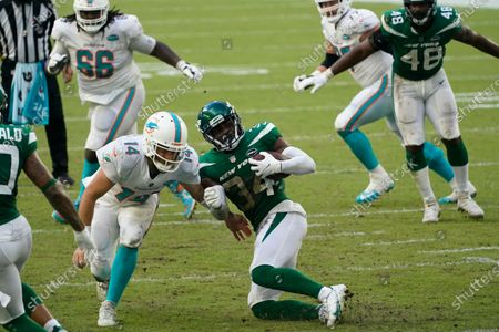 Miami Dolphins quarterback Ryan Fitzpatrick (14) attempts to tackle New York Jets cornerback Brian Poole (34) after Poole intercepted Fitzpatrick's pass, during the first half of an NFL football game, in Miami Gardens, Fla
