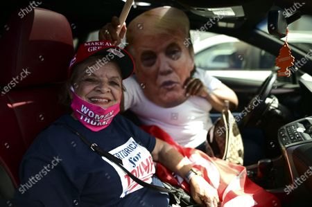 Former senator Miriam Ramírez de Ferrer poses for the camera flanked by a Trump cardboard cutout moments before leaving for the headquarters of the Republican party in support of President Donald Trump's candidacy a few weeks before the presidential election next November, in Carolina, Puerto Rico, . President Donald Trump and former Vice President Joe Biden are targeting Puerto Rico in a way never seen before to gather the attention of tens of thousands of potential voters in the battleground state of Florida