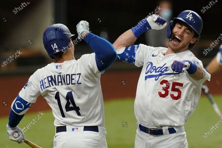 Los Angeles Dodgers' Cody Bellinger, right, celebrates his home run with Enrique Hernandez against the Atlanta Braves during the seventh inning in Game 7 of a baseball National League Championship Series, in Arlington, Texas