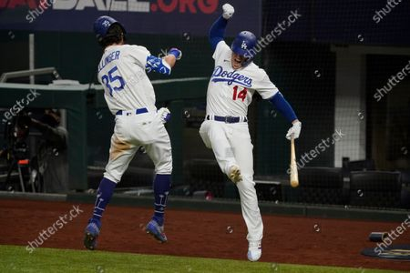 Los Angeles Dodgers' Cody Bellinger celebrates his home run with Enrique Hernandez against the Atlanta Braves during the seventh inning in Game 7 of a baseball National League Championship Series, in Arlington, Texas