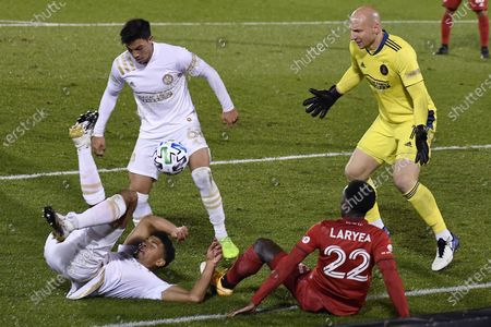 Toronto FC's Richie Laryea, bottom right, falls over Atlanta United's Miles Robinson on a drive to the goal as Atlanta United's Fernando Meza, top left, and Atlanta United goalkeeper Brad Guzan, right, defend during the second half of an MLS soccer match, in East Hartford, Conn