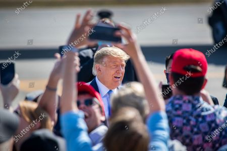 President Donald Trump greets supporters as he arrives on Air Force One at John Wayne Airport on Sunday, Oct. 18, 2020 in Santa Ana, where he will be attending a fundraiser at the home of Palmer Luckey on Lido Island in Newport Beach. (Allen J. Schaben / Los Angeles Times)