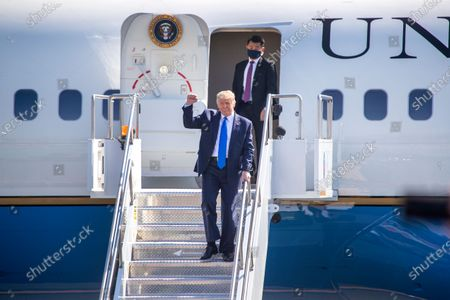 President Donald Trump waves to supporters as he arrives on Air Force One at John Wayne Airport on Sunday, Oct. 18, 2020 in Santa Ana, CA where he will be attending a fundraiser at the home of Palmer Luckey in Newport Beach. (Allen J. Schaben / Los Angeles Times)
