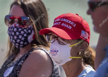 Supporters wear masks as they anticipate President Donald Trump's arrival on Air Force One at John Wayne Airport on Sunday, Oct. 18, 2020 in Santa Ana, CA where he will be attending a fundraiser at the home of Palmer Luckey in Newport Beach. (Allen J. Schaben / Los Angeles Times)