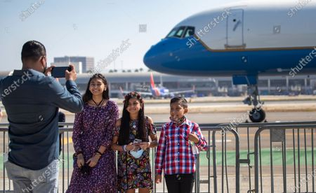 Stock Photo of Trump supporters Hector Franco, left, of Santa Ana, takes a photo of his kids, Mia, 14, Melinda, 12, and Maximo, after seeing President Donald Trump greet supporters upon arrival on Air Force One at John Wayne Airport on Sunday, Oct. 18, 2020 in Santa Ana. Franco said he helped prepare the airport for President Trump's arrival and wanted to share in the experience with his children. President Trump attended a fundraiser at the home of Palmer Luckey in Newport Beach. (Allen J. Schaben / Los Angeles Times)