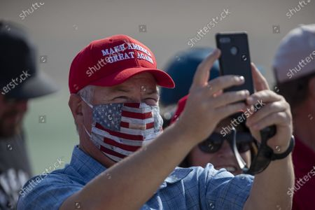 Supporters take photos as they anticipate President Donald Trump's arrival on Air Force One at John Wayne Airport on Sunday, Oct. 18, 2020 in Santa Ana, CA where he will be attending a fundraiser at the home of Palmer Luckey in Newport Beach. (Allen J. Schaben / Los Angeles Times)