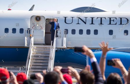 President Donald Trump waves to supporters as he arrives on Air Force One at John Wayne Airport on Sunday, Oct. 18, 2020 in Santa Ana, where he will be attending a fundraiser at the home of Palmer Luckey on Lido Island in Newport Beach. (Allen J. Schaben / Los Angeles Times)