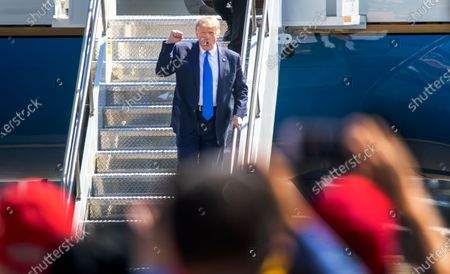 President Donald Trump greets cheering supporters as he arrives on Air Force One at John Wayne Airport on Sunday, Oct. 18, 2020 in Santa Ana, where he will be attending a fundraiser at the home of Palmer Luckey on Lido Island in Newport Beach. (Allen J. Schaben / Los Angeles Times)