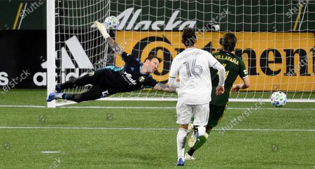 Portland Timbers goalkeeper Steve Clark, left, has the ball go by him for a goal in stoppage time as Los Angeles FC forward Danny Musovski, center, and Portland Timbers defender Jorge Villafana, right, look on during the second half of an MLS soccer match in Portland, Ore., . The match ended in a 1-1- draw